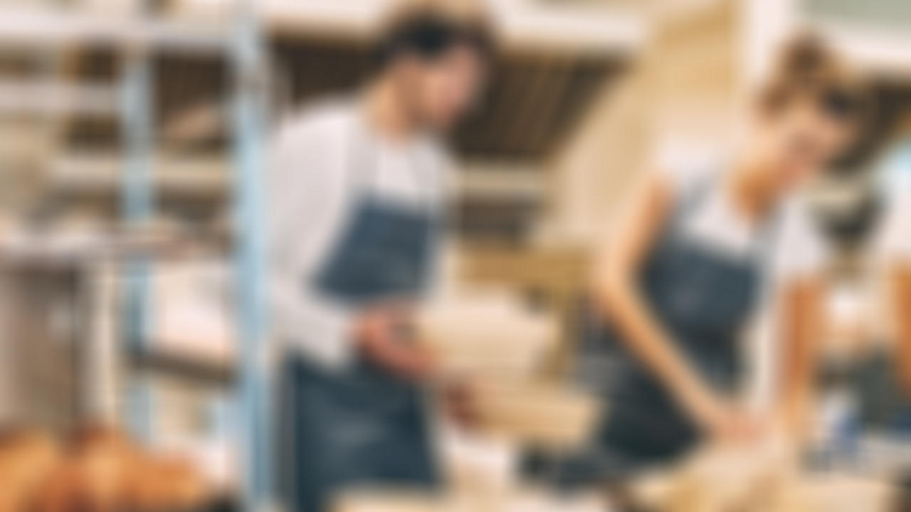 man and woman working in kitchen