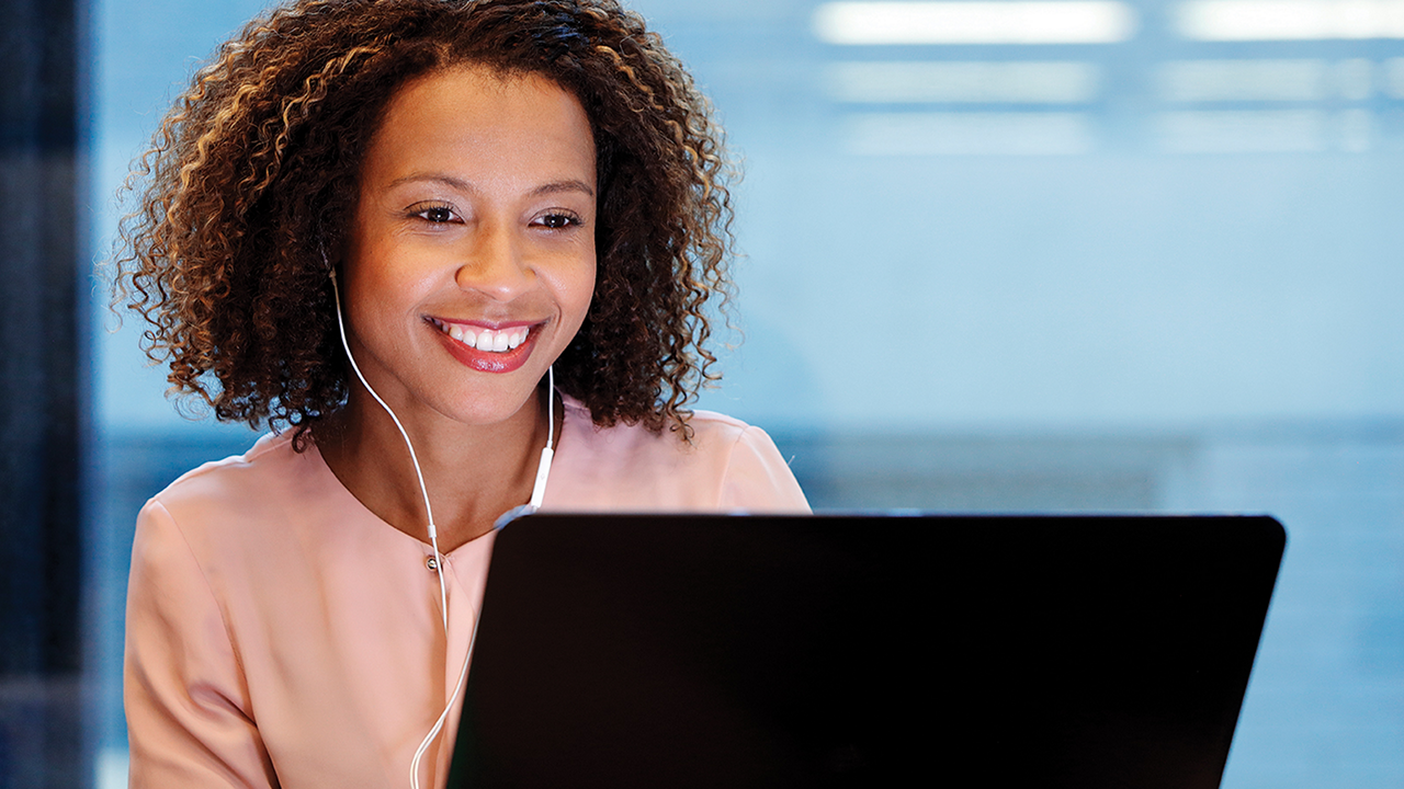 Woman looking at her computer and smiling