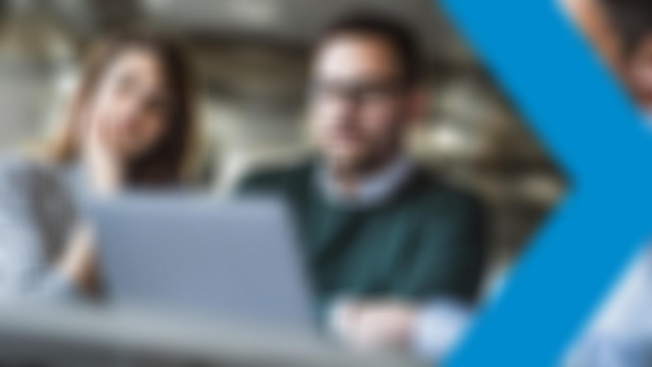 Three bank coworkers using laptop in a meeting in the office.