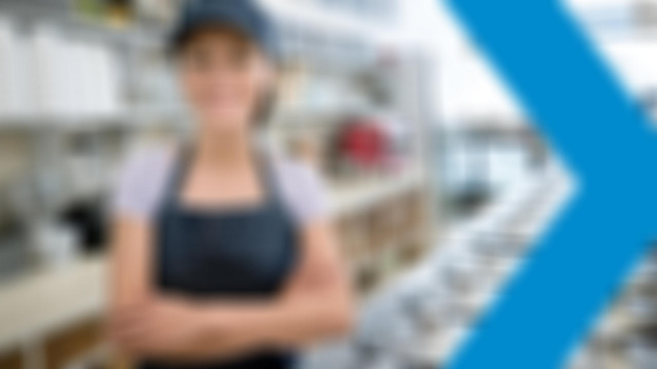 Woman in hat behind service counter smiling at camera