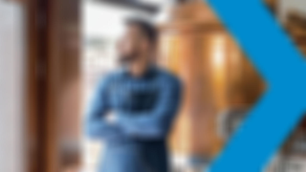 Man looks out window standing in front of distilling tanks