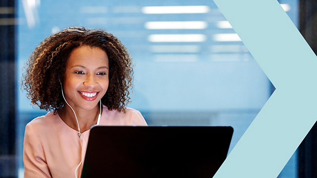 Smiling HR professional wearing headphones and working on laptop.