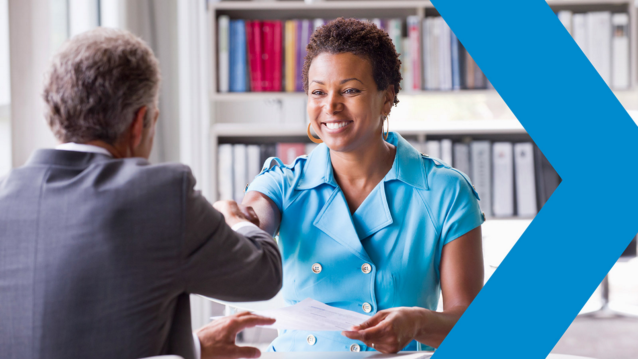 Female HR professional shakes hands with male job candidate.