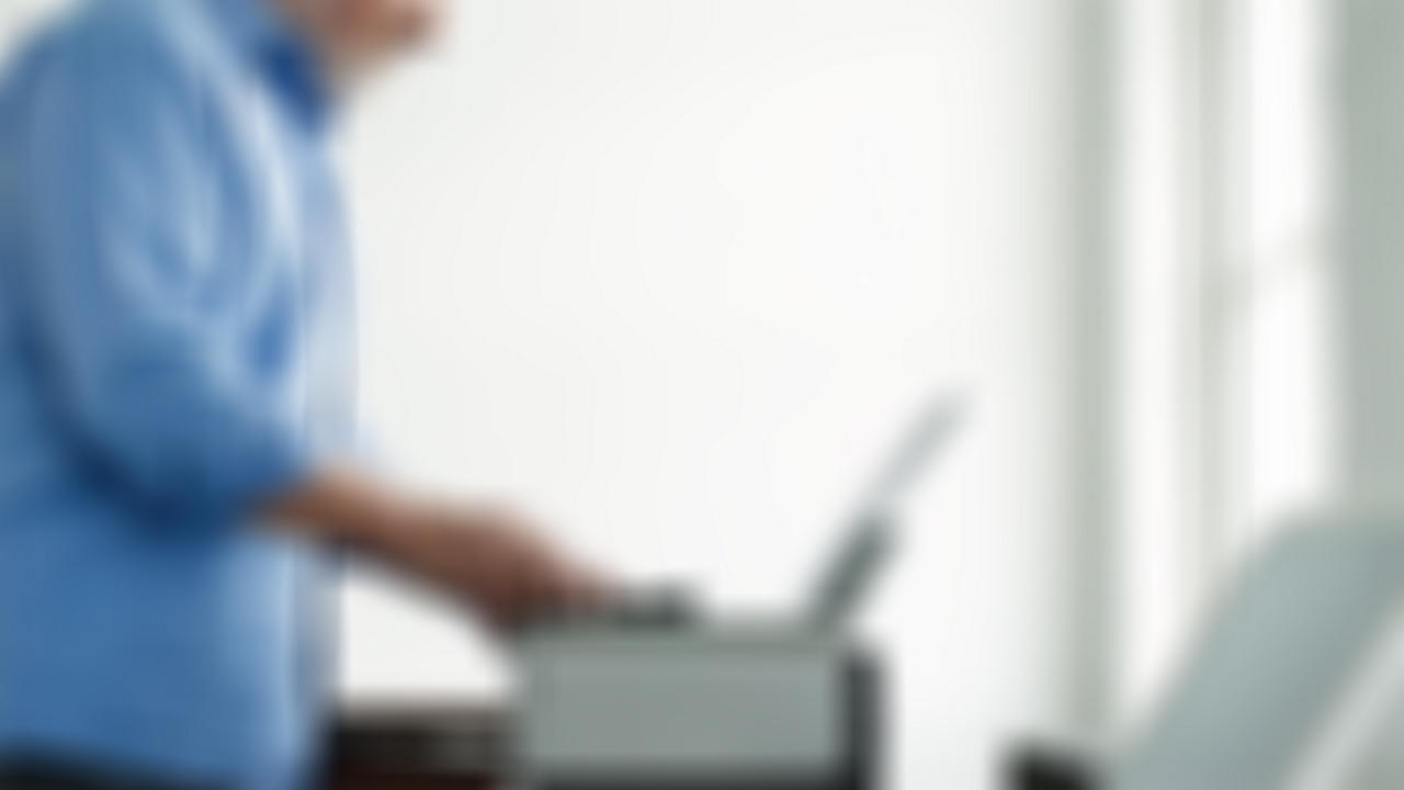 Man printing an eCheck from a printer - image